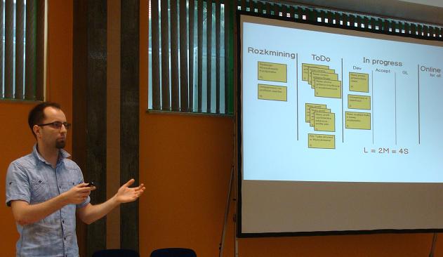 Karol z goldenline.pl podczas prezentacji, w tle portfolio kanban board